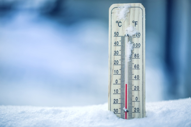 Thermometer on snow shows low temperatures - zero. Low temperatures in degrees Celsius and fahrenheit. Cold winter weather - zero celsius thirty two farenheit
